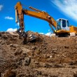 Industrial excavator bulldozer in sandpit with raised bucket — Stock Photo