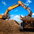 Stock Photo: Excavator loading dumper truck tipper in sandpit