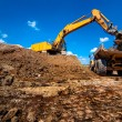 Industrial excavator loading and moving soil material — Stock Photo