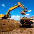 Industrial truck loader excavator moving earth and unloading — Stock Photo