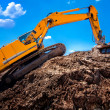 Industrial excavator climbing on soil material — Stock Photo