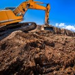 Industrial excavator working on soil material from highway — Stock Photo