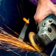 Heavy industry worker cutting steel with angle grinder at car service — Stock Photo #32152927