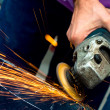 Heavy industry worker cutting steel with angle grinder at car service — Stock Photo