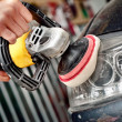 Car headlight cleaning with power buffer machine at service station — Stock Photo