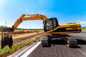 Excavator working on road construction site — Stock Photo