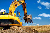 Yellow, heavy duty excavator moving soil — Stock Photo