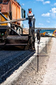 Industrial pavement truck or machine laying fresh bitumen and asphalt — Stock Photo