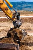 Heavy duty construction excavator loading sand into a dumper truk — Stock Photo
