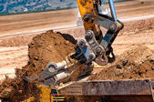 Close-up of heavy duty excavator scoop loading a dumper truck — Stock Photo