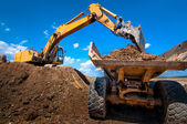 Yellow excavator loading soil into a dumper truck — Stock Photo