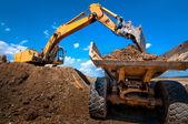 Excavadora amarilla del suelo de carga en un camión volquete — Foto de Stock