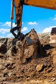 Heavy duty excavator scooping sand and loading dumper trucks — Stock Photo