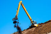 Industrial excavator loading soil material from highway — Stock Photo