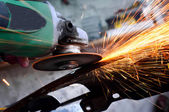 Professional factory grinder cutting through metal and spreading — Stock Photo