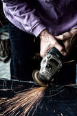 Trabajador industrial usando una pequeña amoladora para corte de metal — Foto de Stock