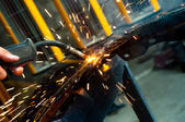 Industrial worker welding with sparks — Stockfoto
