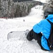Rear view of sportsman with snowboard looking down on difficult slope — Stock Photo