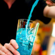 Bartender pours alcoholic drink into cocktail glass making a blue curacao — Stock Photo #32177345