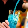 Bartender pours alcoholic drink into cocktail glass making a blue curacao — Stock Photo