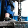 Stock Photo: Close-up of industrial worker drilling hole in metal bar