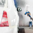 Stock Photo: Automobile engineer spraying paint on white car