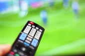 Watching soccer game on modern tv, with a close-up of the remote — Stock Photo