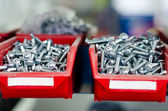 Red cabinets with screws and bolts in a modern factory — Stock Photo