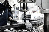 Industrial engineer working on a drilling machine, making a hole — Stock Photo