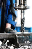 Close-up of industrial worker drilling a hole in a metal bar — Stock Photo
