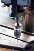 CNC industrial machine making symetrical holes into metallic bar — Stock Photo
