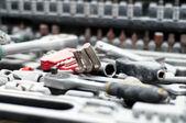 Kit of adjustable metallic tools with mechanical background — Stock Photo