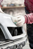 Mechanic prepairing the body of a car for a paint job by appling the first layer of polish — Stock Photo