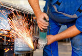 Professional worker in automotive industry grinding metal on a b — Stock Photo