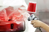 Hand of a worker spraying red glossy paint on a car bumper — Stock Photo