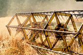 Closeup of harvesting machinery detail while working the field — Stock Photo