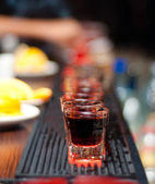 Raw of alcoholic shot drinks on bar — Stock Photo