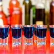 Five blue curacao alcoholic shots on bar with bottles background — Stock Photo