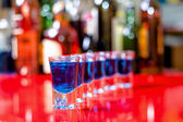 Row of shots on the counter with bar background, first is clear — Stock Photo