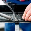 Professional mechanic using a plastic and synthetic welder on bodywork of modern car — Stock Photo