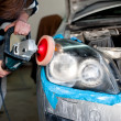 Mechanic cleaning headlights and polishing with power buffer machine. Detail and concept of car care — Stock Photo