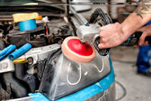 Car care concept with a mechanic cleaning the headlights of a car using a power buffer machine in special garage — Stock Photo
