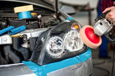 Auto mechanic working on polishing a car headlight with power buffer machine in car care system — Stock Photo