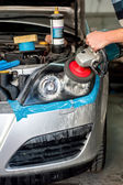 Car Care with Car headlight cleaning with power buffer machine at service station — Stock Photo