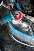 Mechanic cleaning headlights with polishing power buffer machine — 图库照片