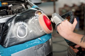 Automotive engineer polishing the headlight of a car at automobile repair and renew service station, using a professional power buffer machine — Stock Photo