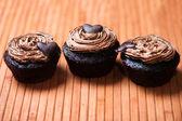 Magdalenas cremosos chocolate dulces con corazón como una galleta en la parte superior — Foto de Stock