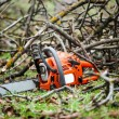 Gasoline professional chainsaw cutting branches against wood background — Stock Photo