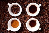 Four different mugs of coffee, ground, coffee beans, liquid coffee and empty mug, isolated on fresh african coffee background — Stock Photo
