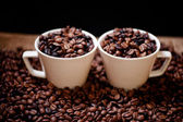 Fresh hot columbian coffee in two cups, around coffee beans and cloth — Stock Photo